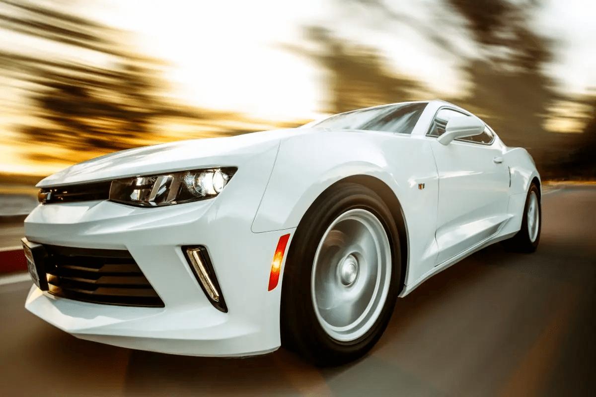 Lähikuvassa valkoinen huippuauto ajamassa lujaa