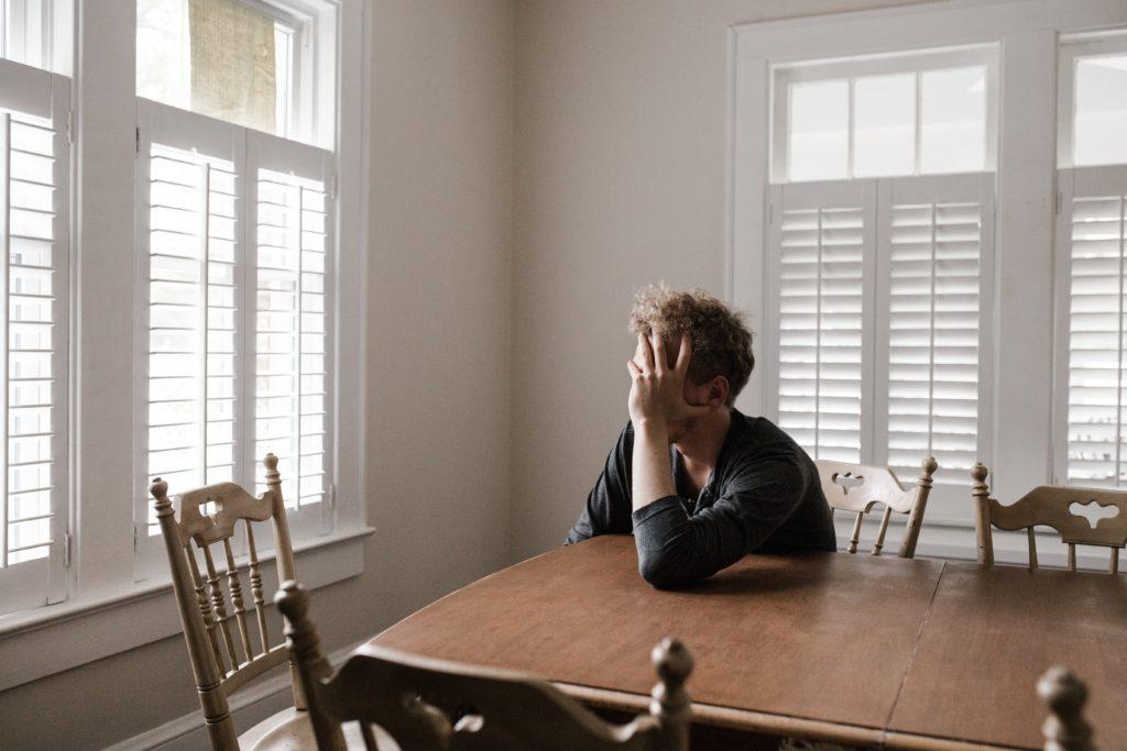 Mies istuu tuolilla ja nojaa kädellään ruskeaa pöytää vasten
