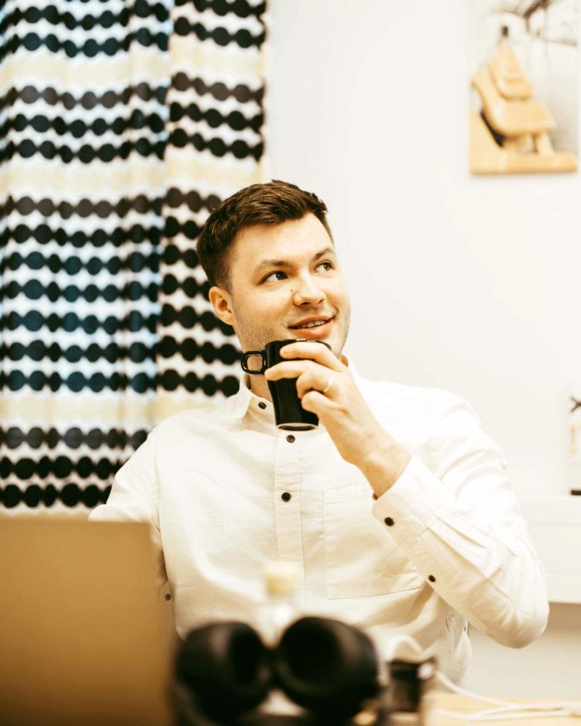 Myyjä juo kahvia työpöydän äärellä palaverin aikana työpaikalla.