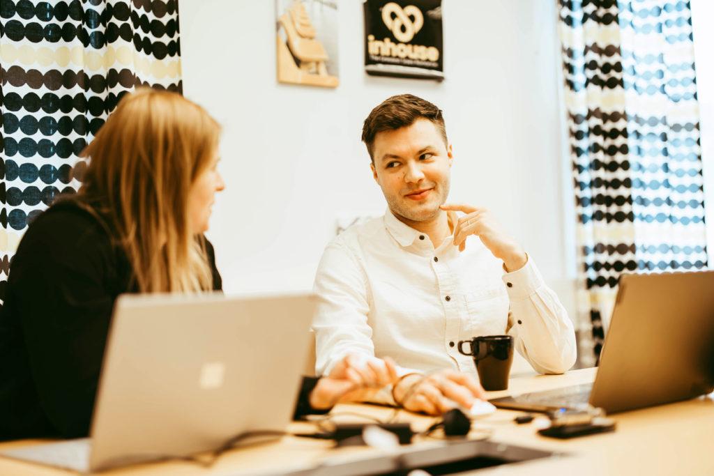Myyjät keskustelemassa työpöydän äärellä työhuoneessa toimistolla.